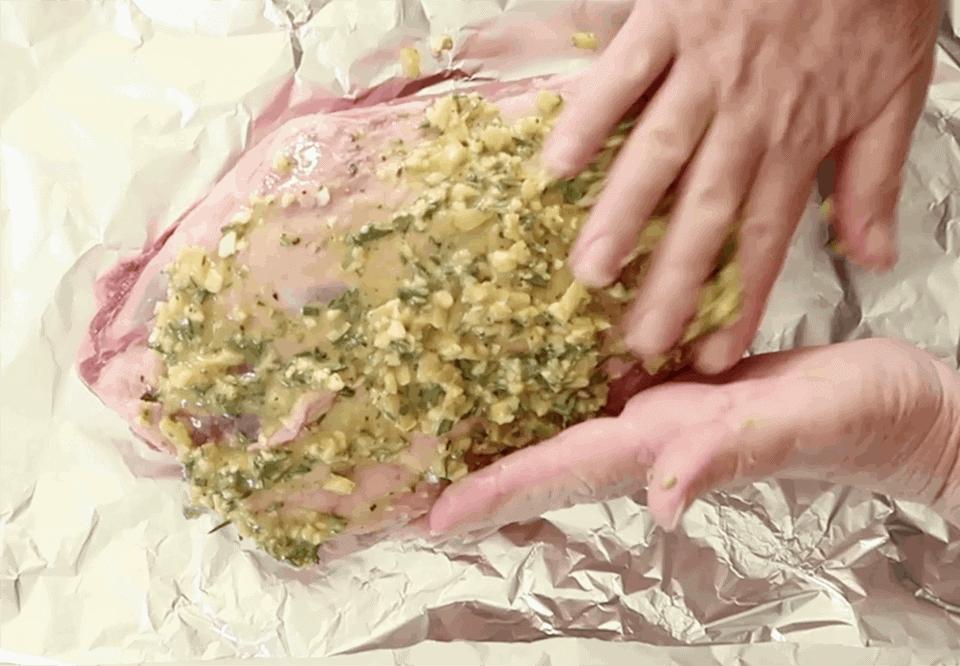 massaging lemon and herbs into lamb shoulder to make Slow Roasted Greek Shoulder of Lamb