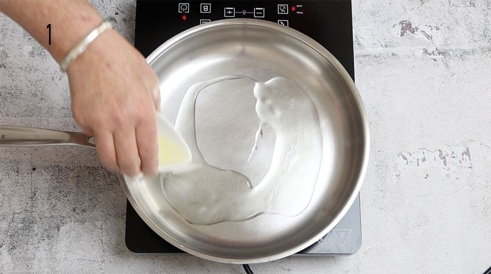 adding oil to a stainless steel frying pan
