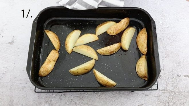 potato wedges in a black baking tray to make chicken fennel lemon tray bake