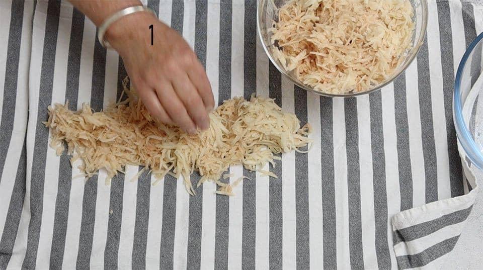 adding potato to teatowel ready to wring to make Crispy Hash Browns