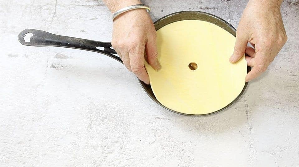 placing the pastry over the apples in a frying pan to make Apple Tarte tatiT