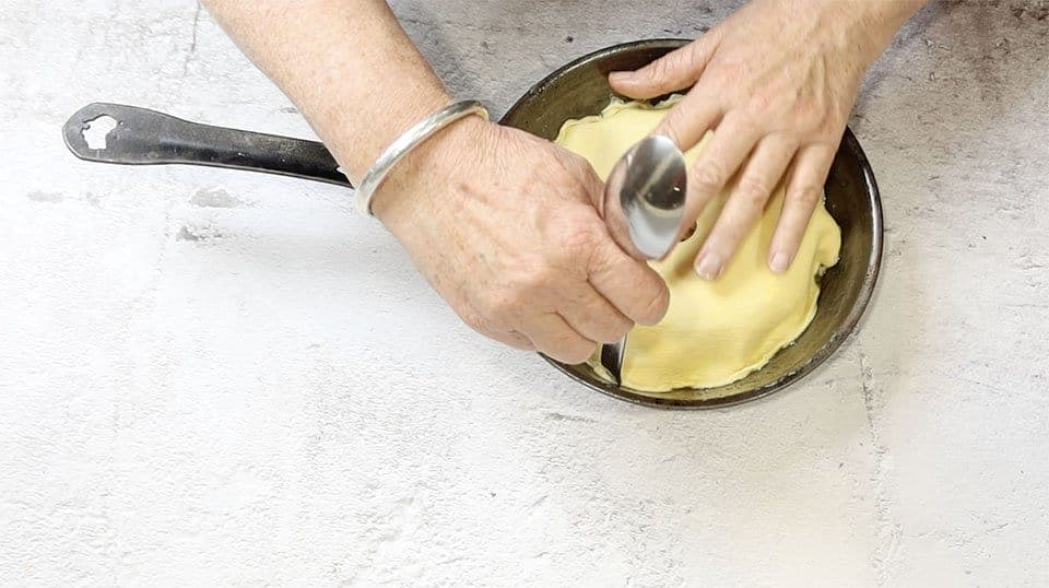 pushing pastry into place with a spoon to make Apple Tarte Tatin