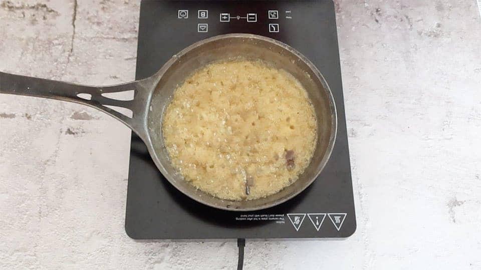 caramel ingredients bubbling in a frying pan on a hot plate to make apple tarte tatin