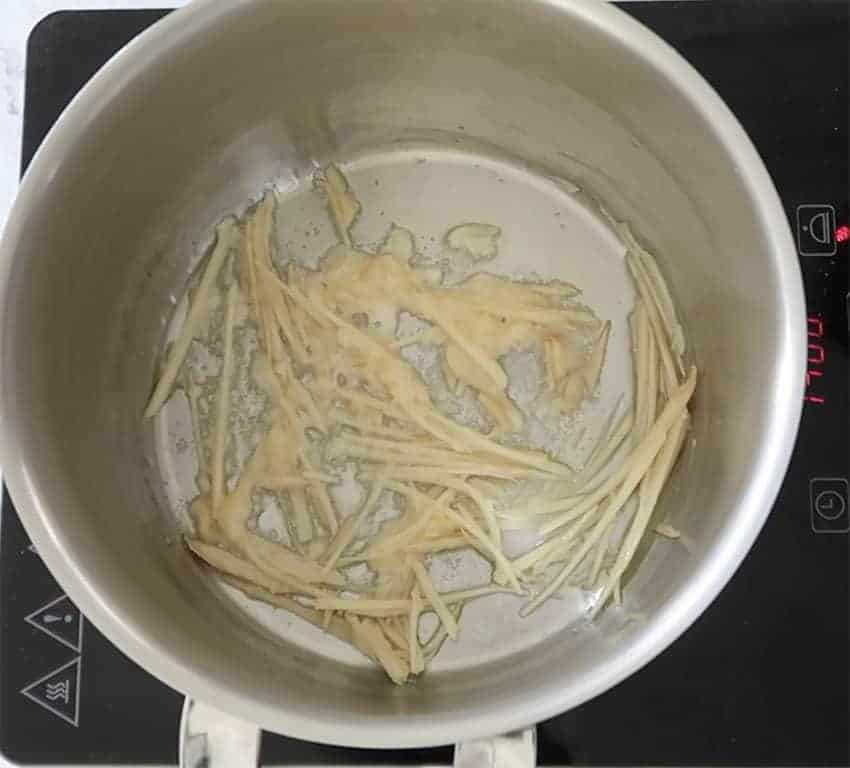 chinese chicken noodle soup sauteeing the garlic and ginger off in oil in a silver saucepan