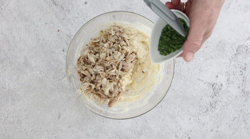 crab meat added to a bowl to make Cajun crab tarts