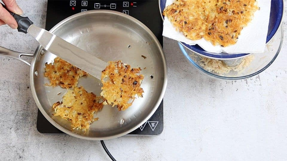 Crispy Hash Browns cooked and golden being transferred to a warming tray