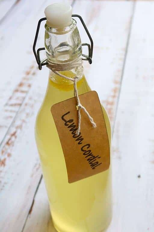 homemade lemon cordial in a bottle with a brown paper label tied with string