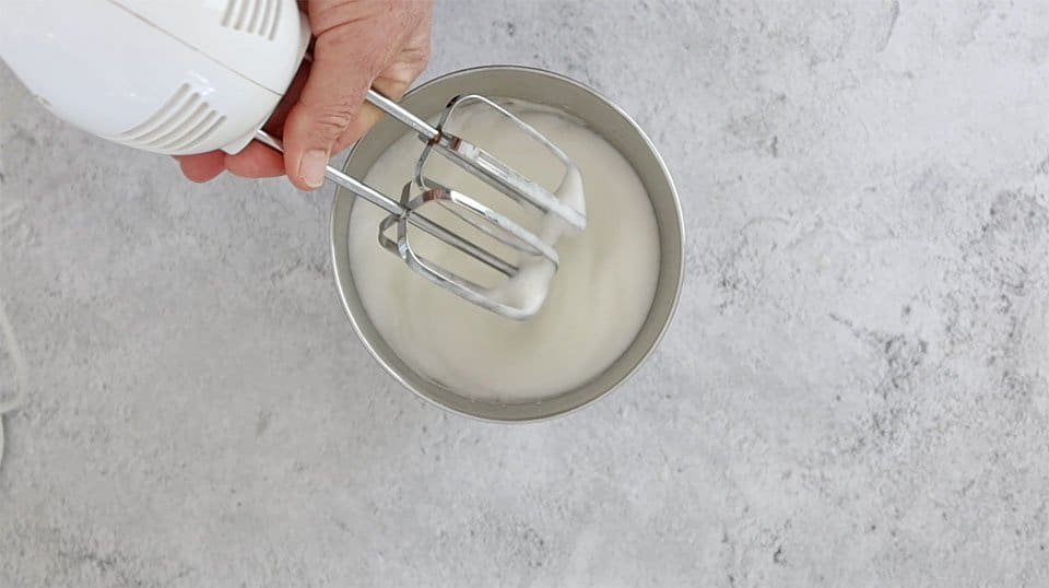 beating egg whites in a metal bowl with a hand mixer to make Upside Down Lemon Delicious