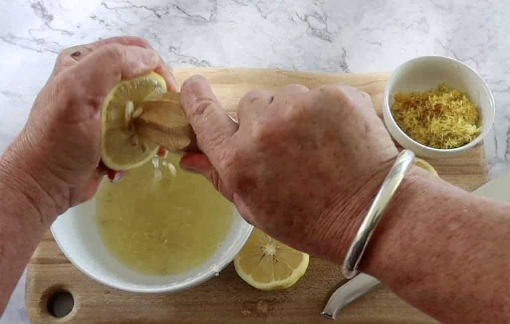 homemade lemon cordial juicer lemons with a wooden reamer over a white bowl