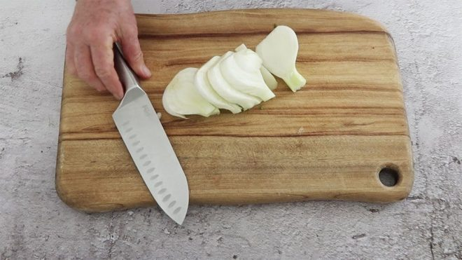 thick cut slices of fennel on a timber chopping board with a knife ready to prepare to make Chicken Fennel Lemon Tray Bake