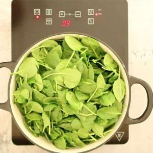 baby spinach in a saucepan ready to be cooked to make Steakhouse Creamed Spinach