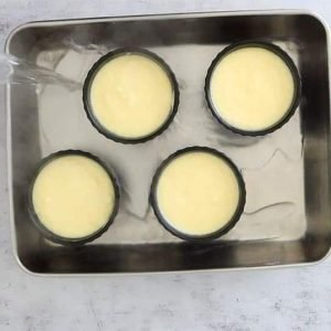 ramekin dishes filled with Upside Down Lemon Delicious batter in a baking dish with water being added