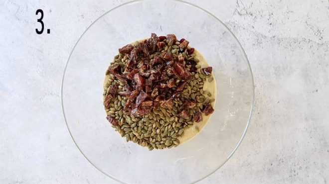 adding nuts and fruit to a glass bowl with batter to make Homemade Gourmet Crackers