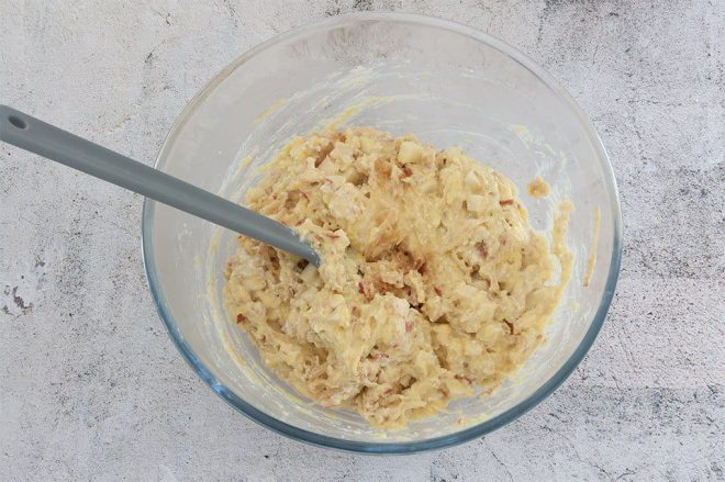 Batter to make Polenta Apple and Ricotta Fritters in a glass bowl ready to fry