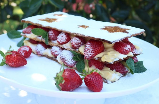 Mille Feuille with Berries on a white plate with greenery in the background