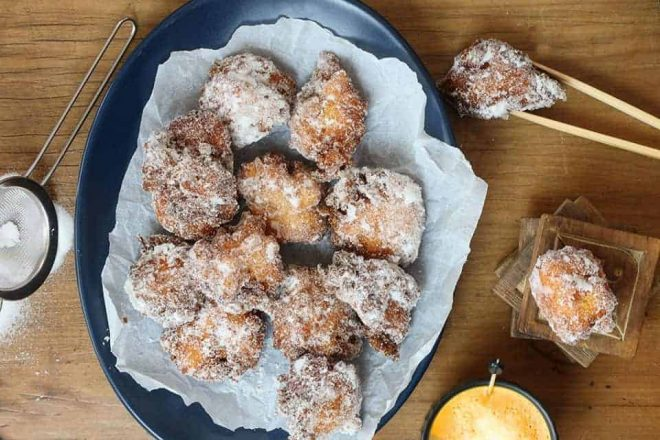 Polenta Apple and Ricotta Fritters served on a blue plate on a timber table