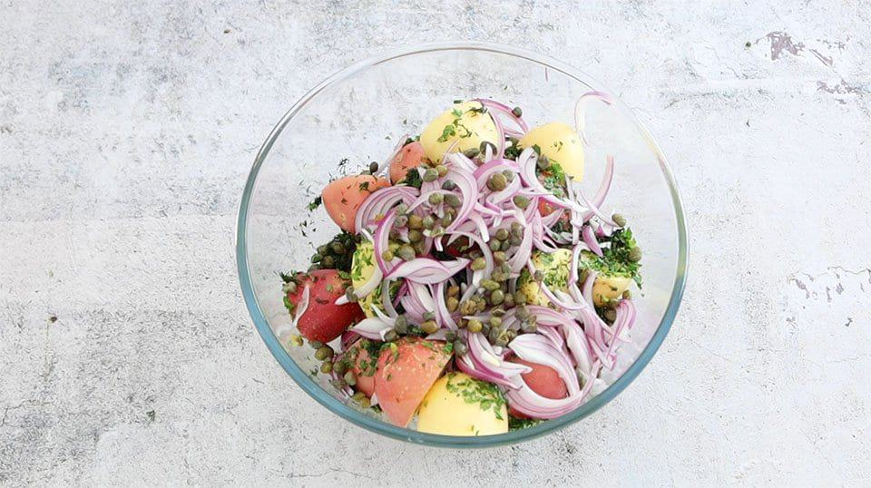 Ingredients to make No-Mayo Potato Salad combined in a glass bowl