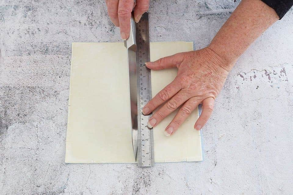 cutting puff pastry to make Mille Feuille with Berries