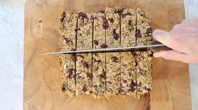 freshly cooked Homemade Granola Bars on a chopping board with a knife cutting into slices