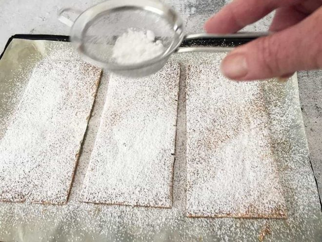 dusting cooked sheets of pastry with icing sugar to make Mille Feuille with Berries
