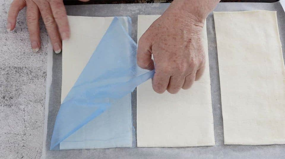 laying uncooked pastry rectangles onto a baking sheet to cook for Mille Feuille with Berries