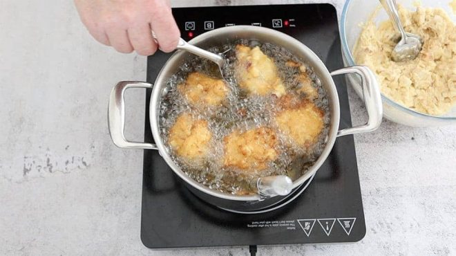 Polenta Apple and Ricotta Fritters frying in a saucepan