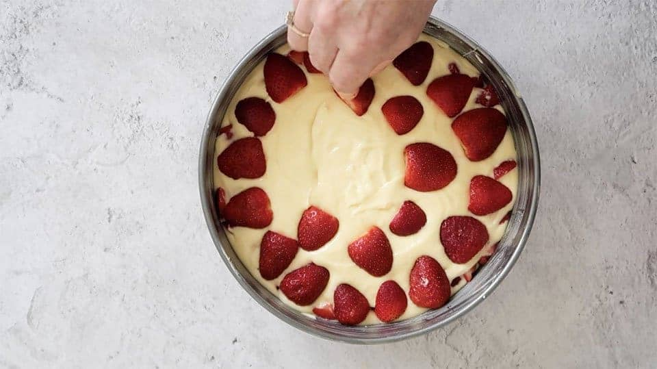 cake batter in cake tin with strawberries arranged on top to make Strawberry Sour Cream Cake