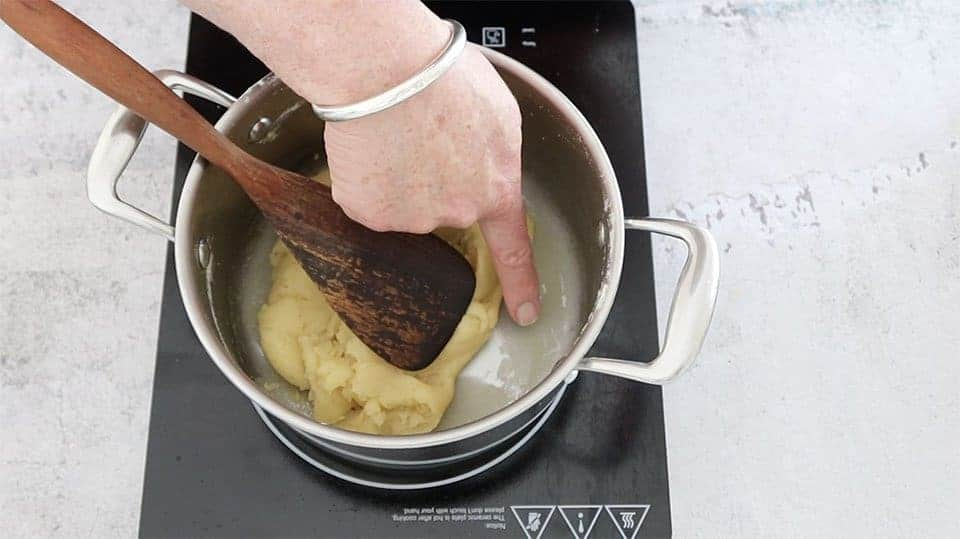 a silver pot with dough and a wooden spoon and a finger pointing to the skin on the pan to show the steps for the The Definitive Guide to Making Choux Pastry
