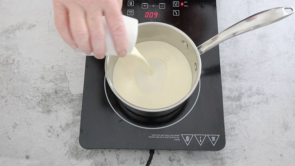 adding cream to a pot to heat to make Whipped Creamy Mashed Potatoes