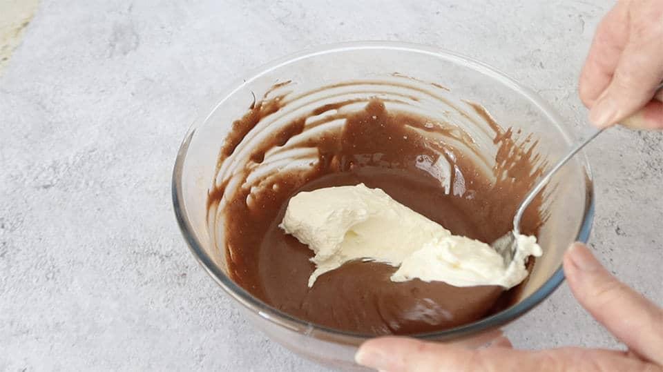 adding beaten cream to the chocolate condensed milk mixture to make No Churn Chocolate Chunk Ice Cream