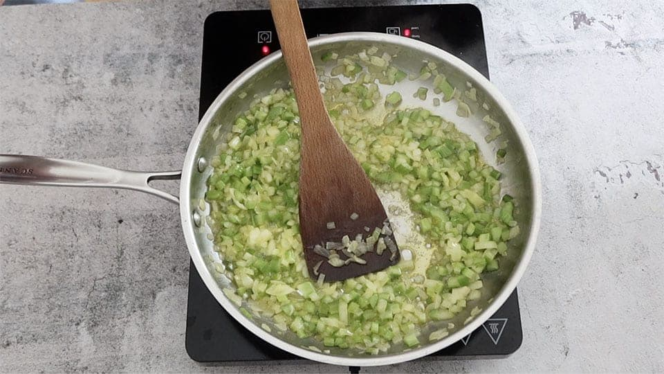 celery and onion sauteed in a silver frying pan to make Mum's Simple Classic Turkey Stuffing