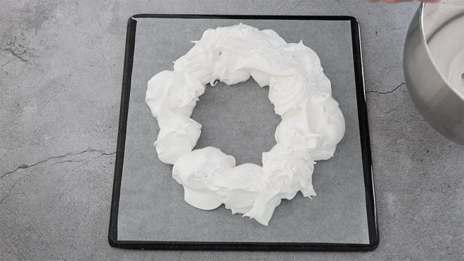 Placing a second layer of meringue mixture onto the christmas pavlova wreath