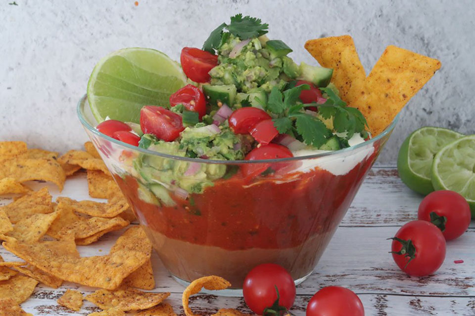 quick Mexican layered dip in a glass bowl on a timber table