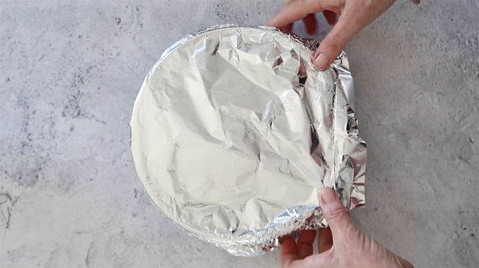 bacon and cheese strata covered with foil and hands crimping the foil