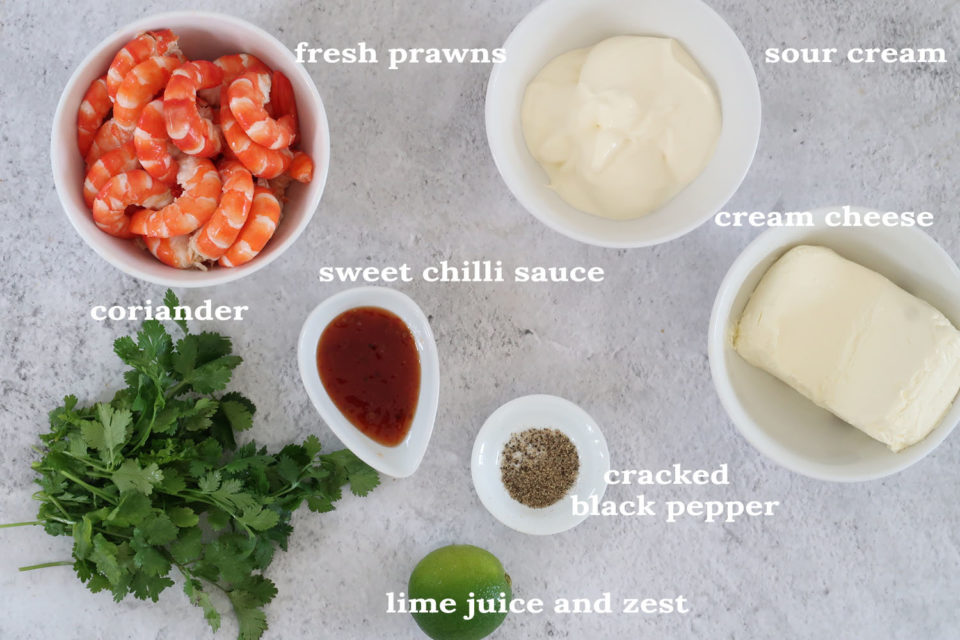 Ingredients to make Prawn coriander and sweet chilli dip in white bowls on a concrete table