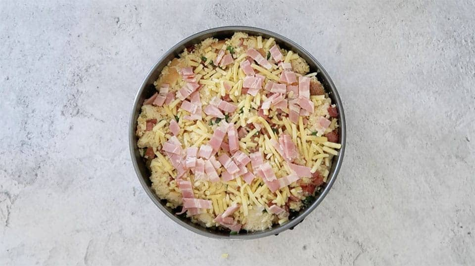 sprinkling bacon and cheese over the Bacon and Cheese Strata in a springform tin